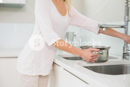 Woman filling pot with water