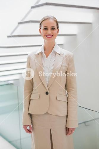 Smiling stylish businesswoman standing next to stairs