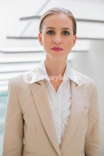 Unsmiling stylish businesswoman standing next to stairs