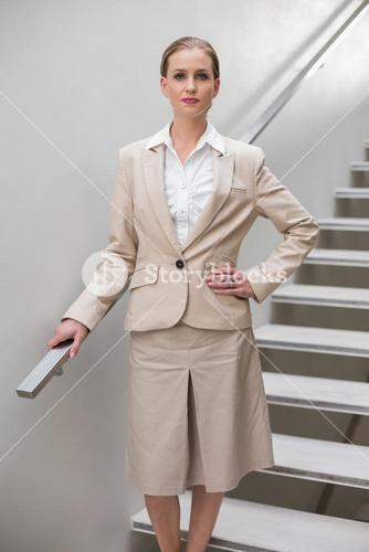 Unsmiling stylish businesswoman standing with hand on hip