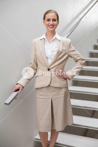Smiling stylish businesswoman standing with hand on hip