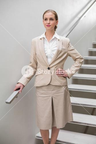 Serious stylish businesswoman standing with hand on hip