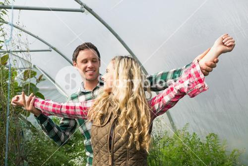 Sweet couple posing in their greenhouse