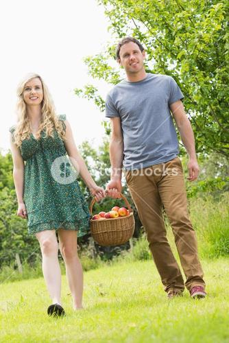 Sweet couple carrying a basket of apples