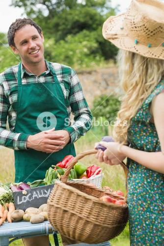 Young farmer selling organic vegetables to pretty blonde
