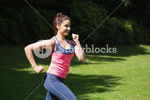 Fit woman running in the sunshine