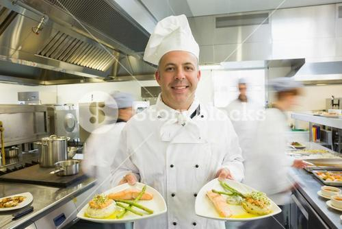 Mature head chef presenting proudly two dinner plates