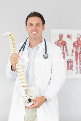 Handsome cheerful doctor holding skeleton model