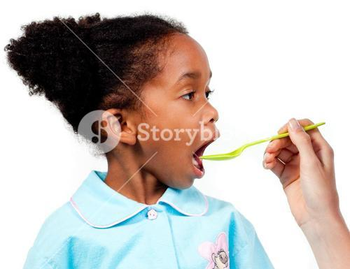 Close up of a cute little girl taking medicine