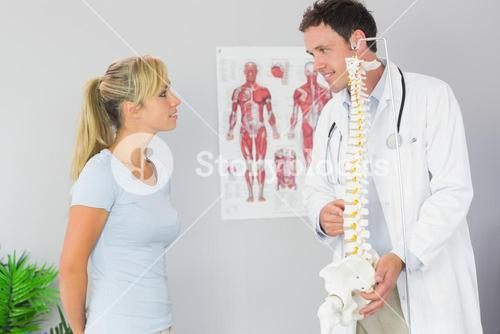 Content doctor holding skeleton and talking to patient