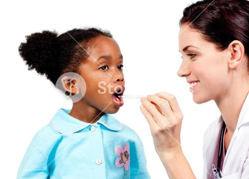 Smiling doctor taking little girls temperature