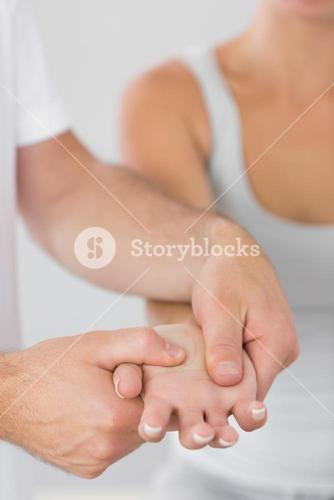 Physiotherapist examining patients hand