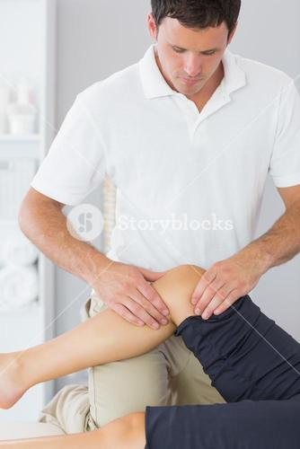 Handsome physiotherapist controlling knee of a patient