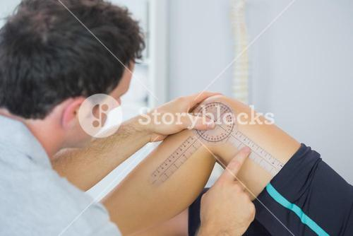 Physiotherapist checking knee with goniometer