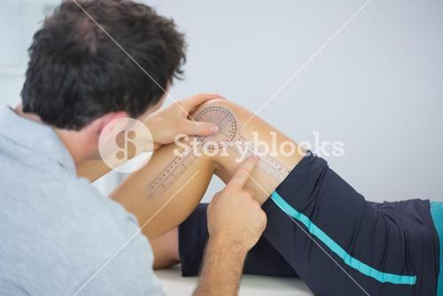 Physiotherapist measuring knee with goniometer