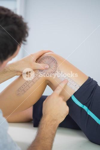 Physiotherapist examining knee with goniometer