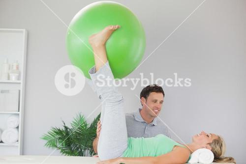 Patient holding exercise ball between legs