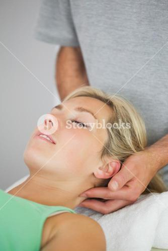 Physiotherapist holding patients head