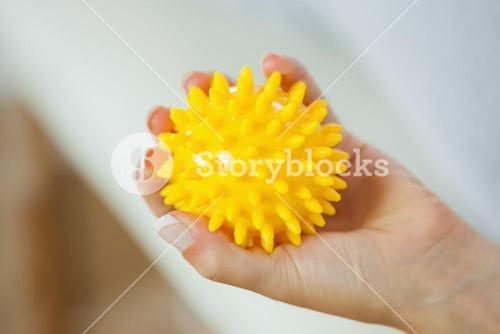 Close up of female left hand holding yellow massage ball