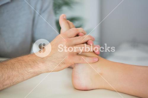 Physiotherapist treating patients foot