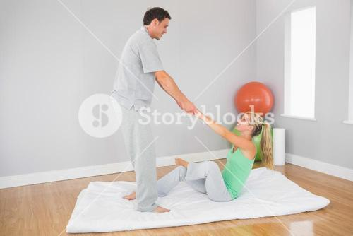 Content physiotherapist helping patient doing exercise
