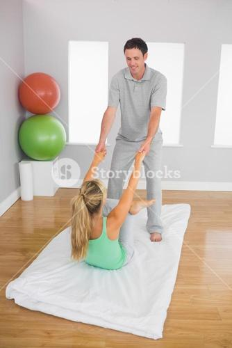 Smiling physiotherapist helping patient doing exercise
