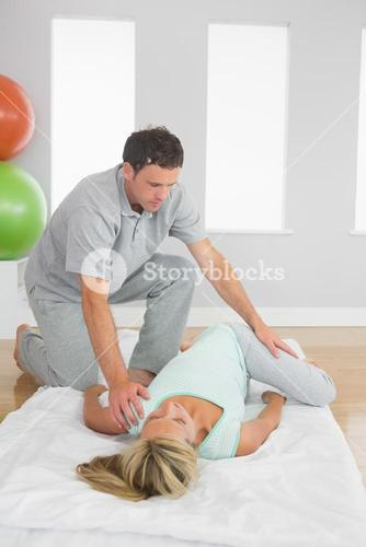 Physiotherapist examining patients hips on a mat on the floor