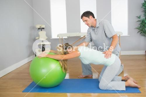 Physiotherapist controlling patient doing exercise with exercise ball