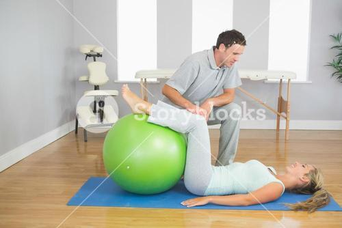 Physiotherapist checking patient doing exercise with exercise ball