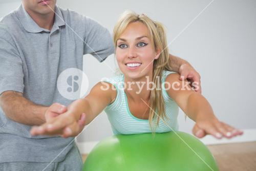 Physiotherapist correcting patient doing exercise on exercise ball