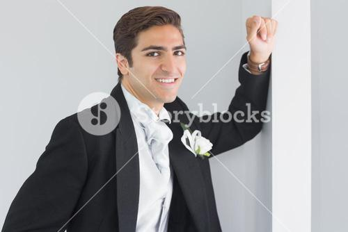 Handsome bridegroom leaning against a wall