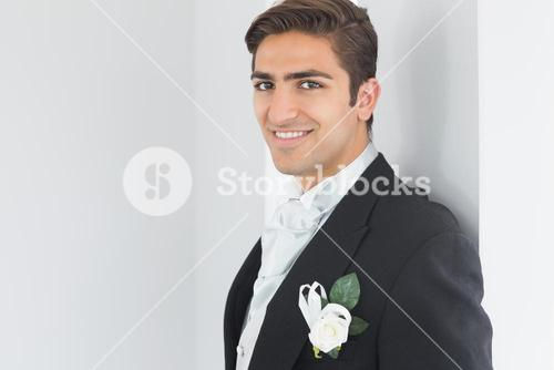 Cute bridegroom leaning against a wall