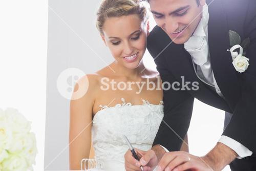 Happy young bridegroom signing wedding contract
