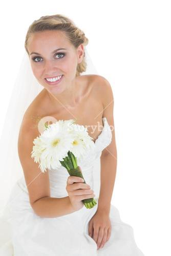 Content young bride sitting on floor holding a bouquet