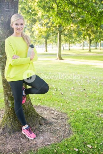Fit cheerful blonde holding sports bottle