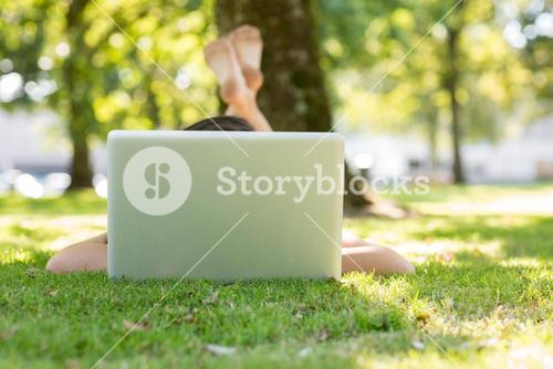 Brunette lying on the grass typing at her laptop