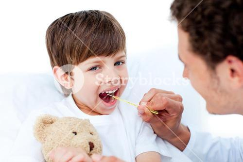 Young doctor taking little boys temperature