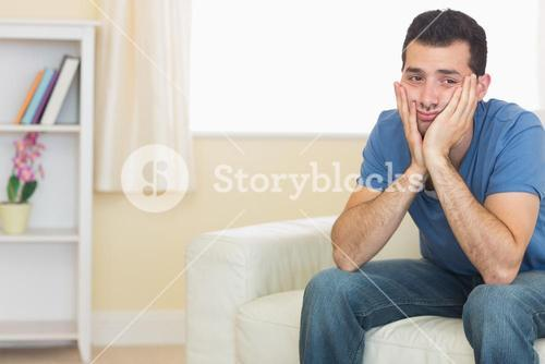Casual upset man sitting on couch