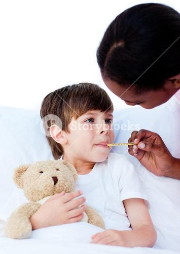Female nurse taking childs temperature