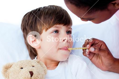 Close up of a doctor taking childs temperature