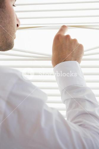 Attractive businessman spying through roller blind