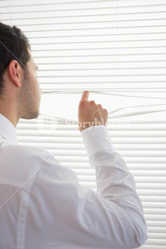 Rear view of attractive businessman spying through roller blind