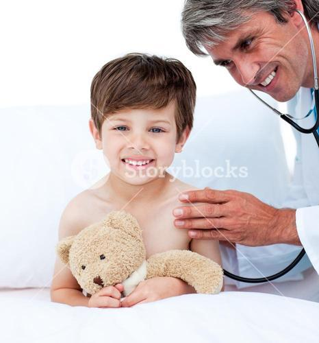 Mature doctor checking little boys pulse