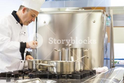 Concentrated head chef stirring in pot