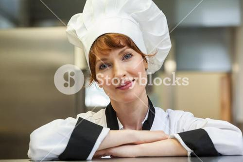 Pretty smiling head chef looking at camera