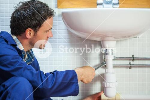 Handsome happy plumber repairing sink