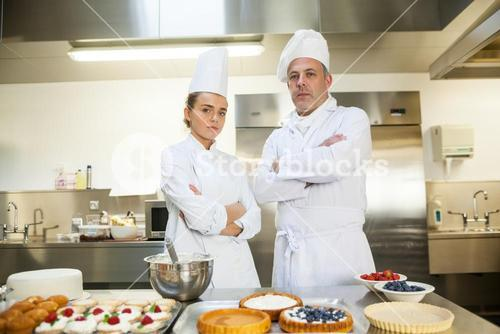 Serious chef and head chef standing arms crossed