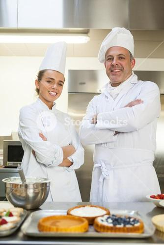 Smiling chef and head chef standing arms crossed