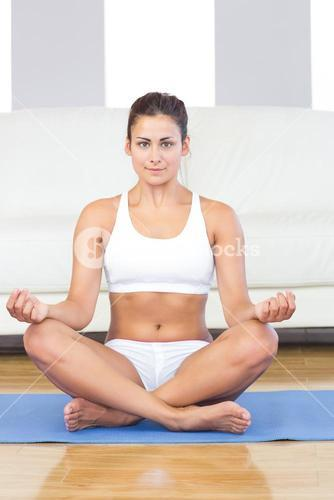 Pretty sporty woman in sportswear sitting on an exercise mat in her living room
