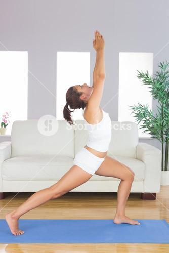 Pretty brunette woman stretching her body in yoga pose